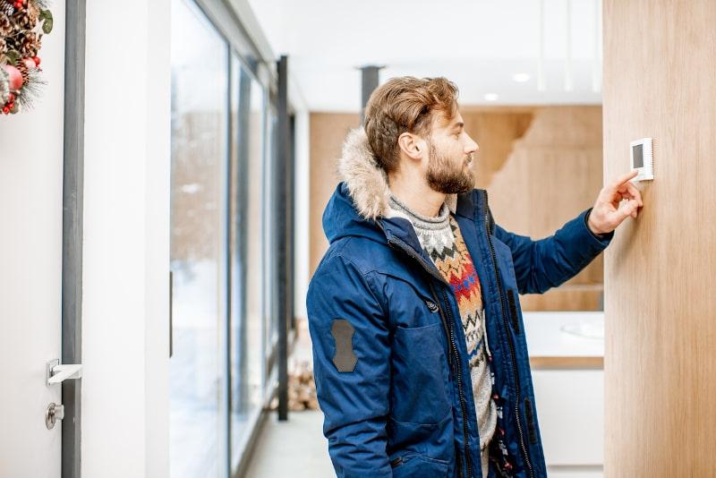 Cold Man Adjusting Thermostat